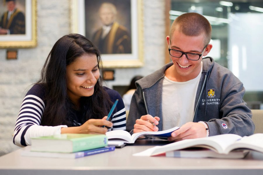One University of Manitoba student happily tutoring another student in an on campus library.