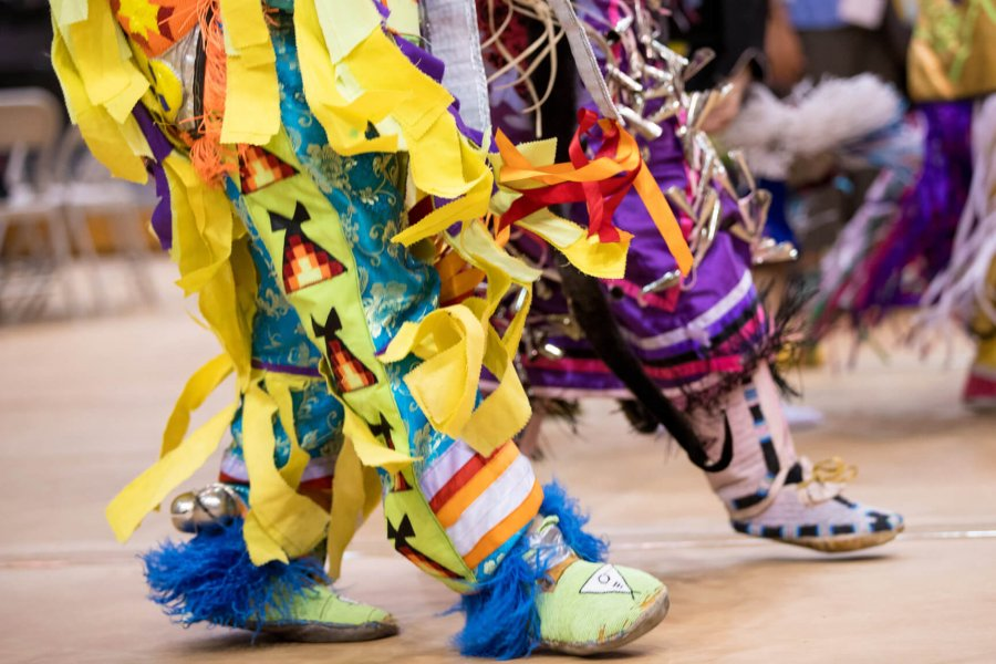 Pow Wow dancers' feet in colourful regalia during Traditional Graduation Pow Wow.