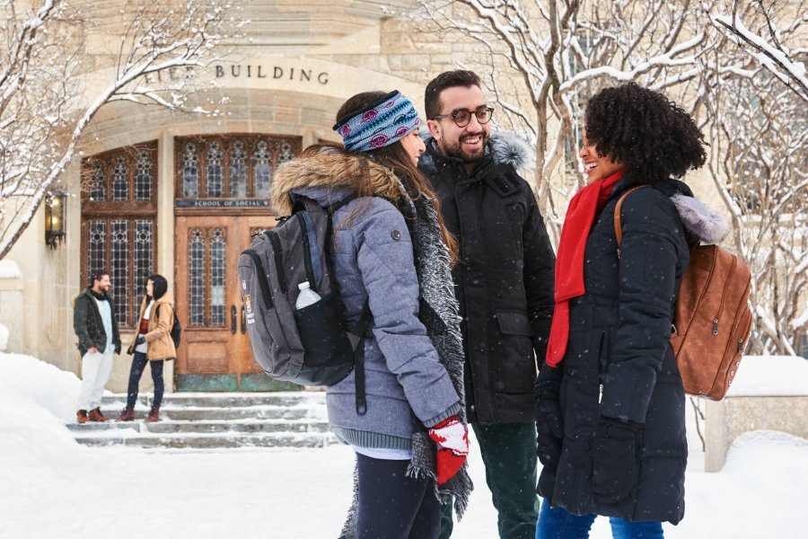 Three smiling international students talking outdoors on a snowy winter day.