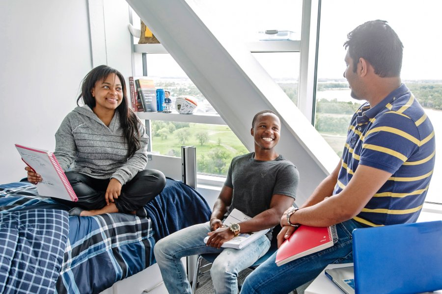 Three University of Manitoba students sitting in a Pembina Hall Residence room.