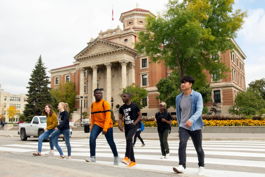 A group of University of Manitoba students walking across the street in front of the Administration building.
