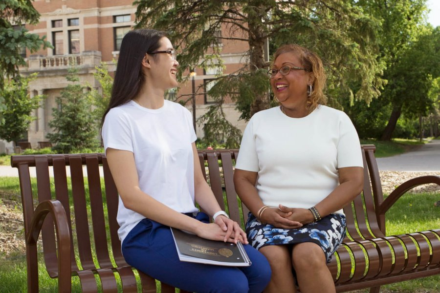 Two students sit chatting on a bench outside on campus.