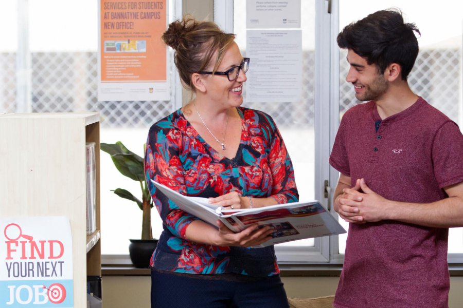 A University mentor stands holding a binder while providing career information to a student.