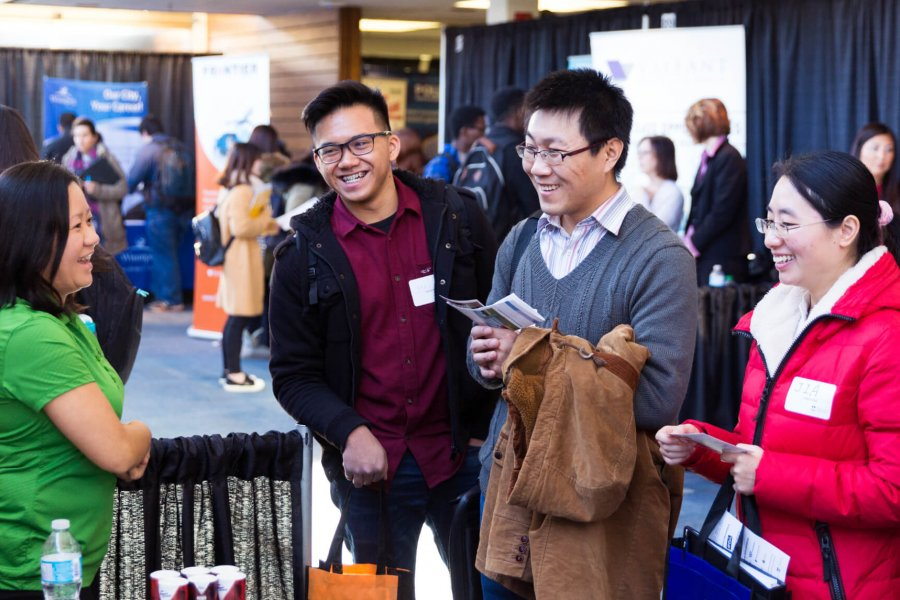 Three students chat with a potential employer at a career fair display booth.