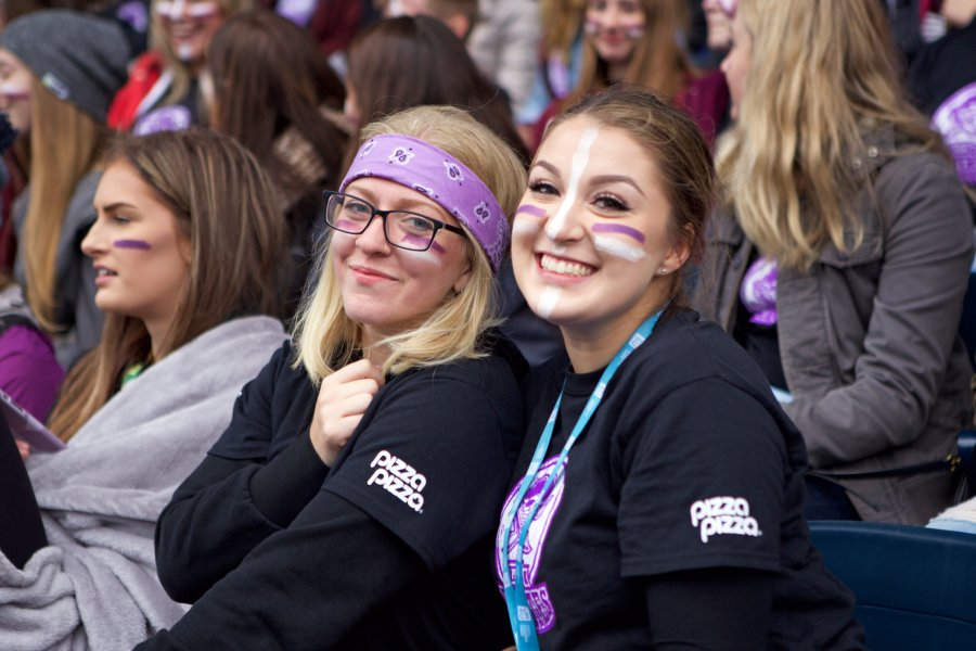Two female University of Manitoba students showing off their team spirit at a Bisons Football game.