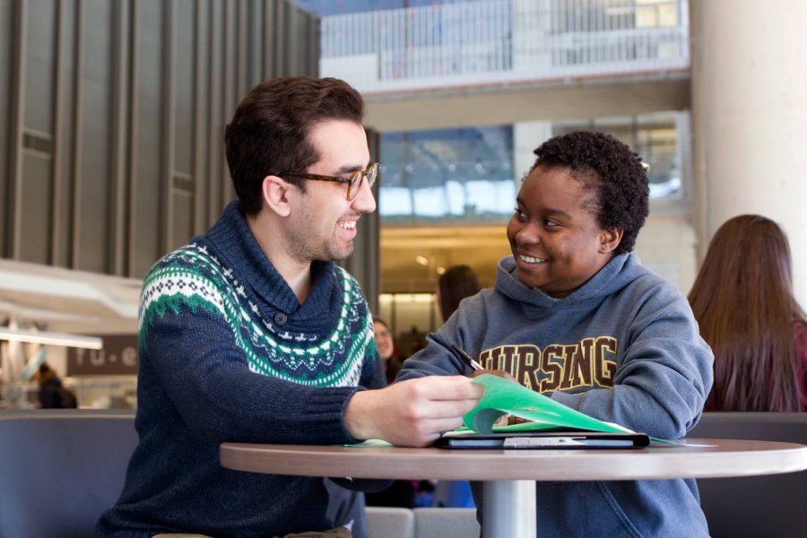 Two international students sit at a table, chatting and reviewing printed material.
