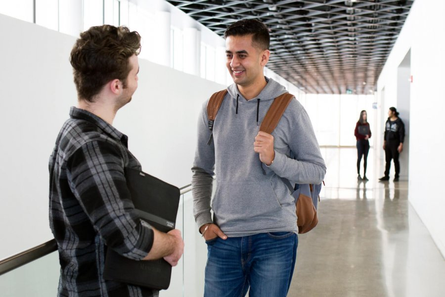An international graduate student chats with a mentor in a UM hallway.