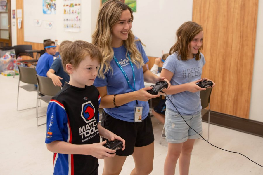 Two Mini U juniors play a video game with their leader.