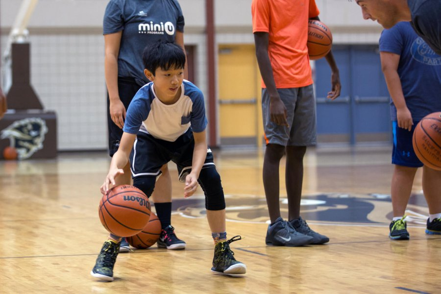 A Mini U junior dribbles a basketball during a game.