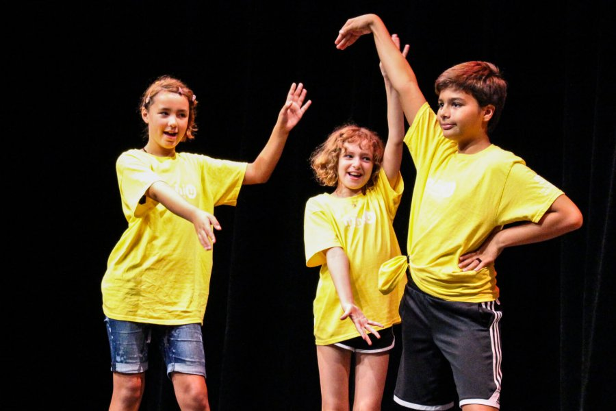 Three Mini U participants on stage during a group performance.