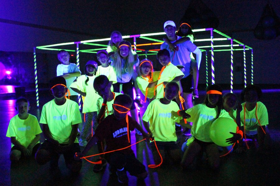 A group of Mini U juniors and their leaders posing for a group photo in a dark room with neon glowing t-shirts.