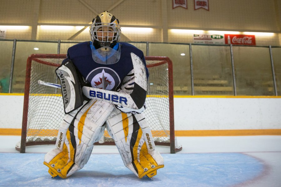 A junior goalie stands at the net ready to block a shot.