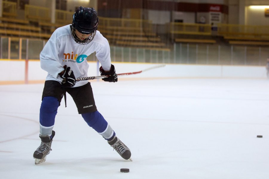 A junior hockey player practices taking shots.