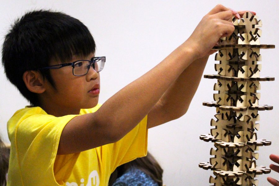 A child builds a tower out of interlocking wooden blocks.