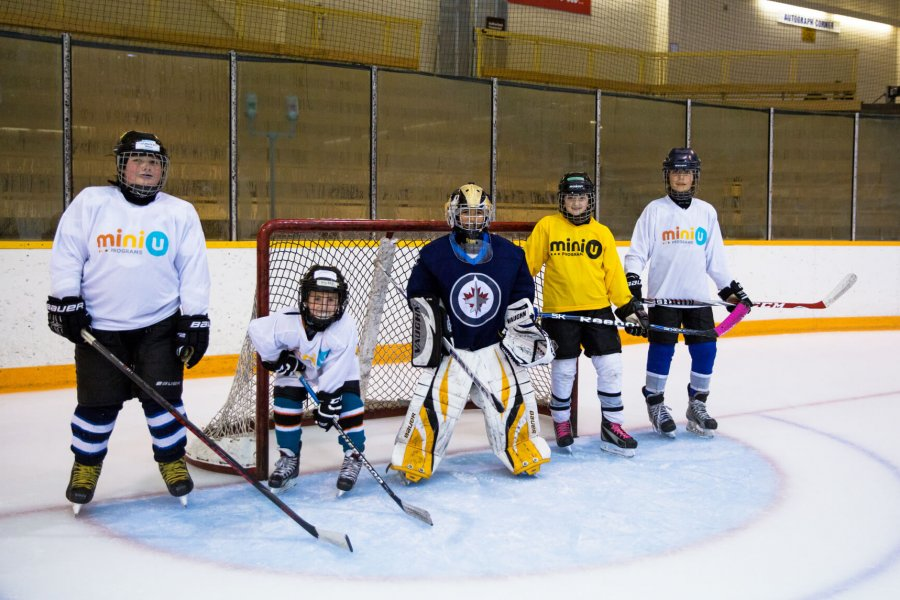 A group of five hockey players stand at the net.