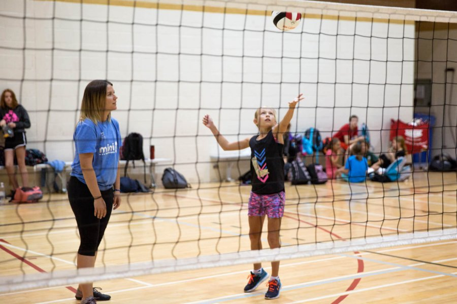 A junior volleyball player serves the ball.