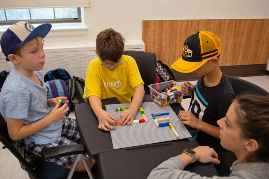 A group of juniors sit at a table playing with Lego.