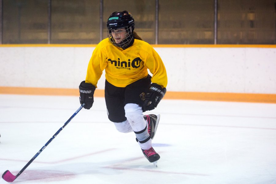 A mini U junior hockey player skating.