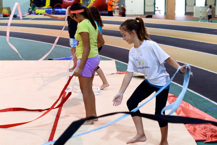 A group of kids playing with colourful rhythmic gymnastics ribbons.