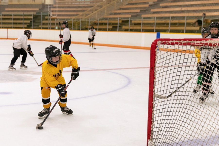 A junior hockey player takes a shot at a net.