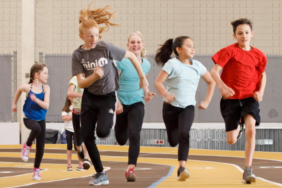 Several children racing each other on an indoor running track.