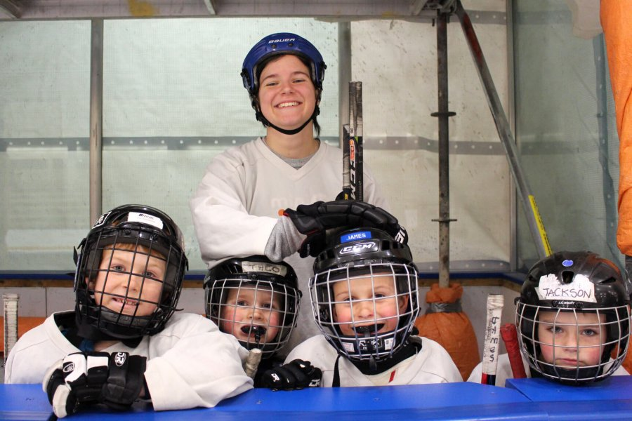 Kids and their Mini U leader getting ready to go on the ice.