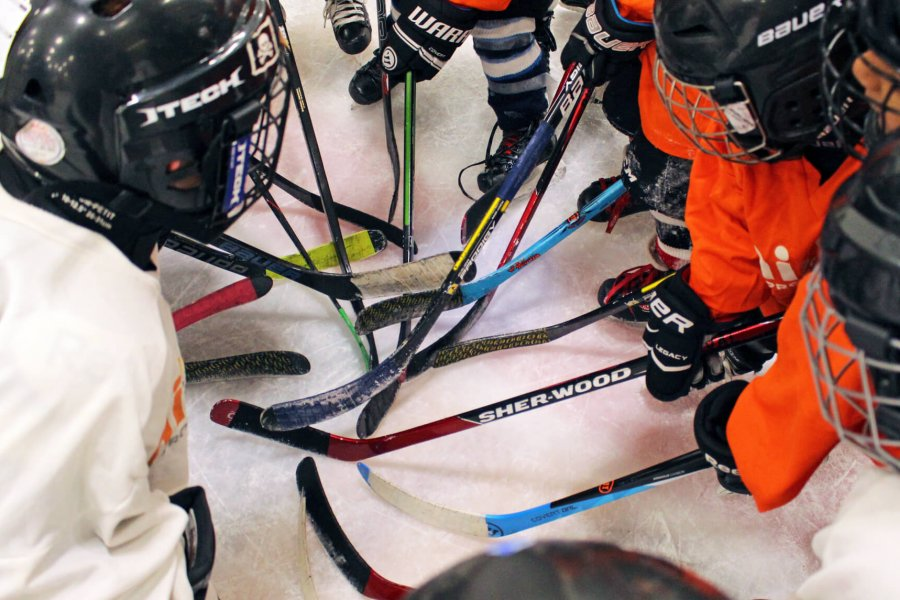 A group of Mini U skaters huddle with their hockey sticks together.
