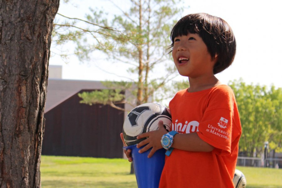 A Mini U participant holds a soccer ball.