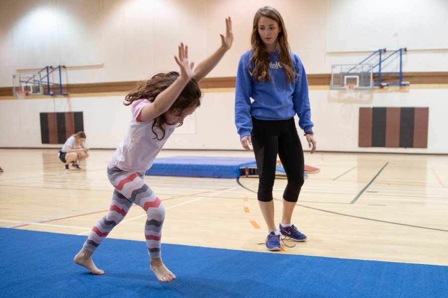A Mini U leader watches a participant doing a cartwheel.