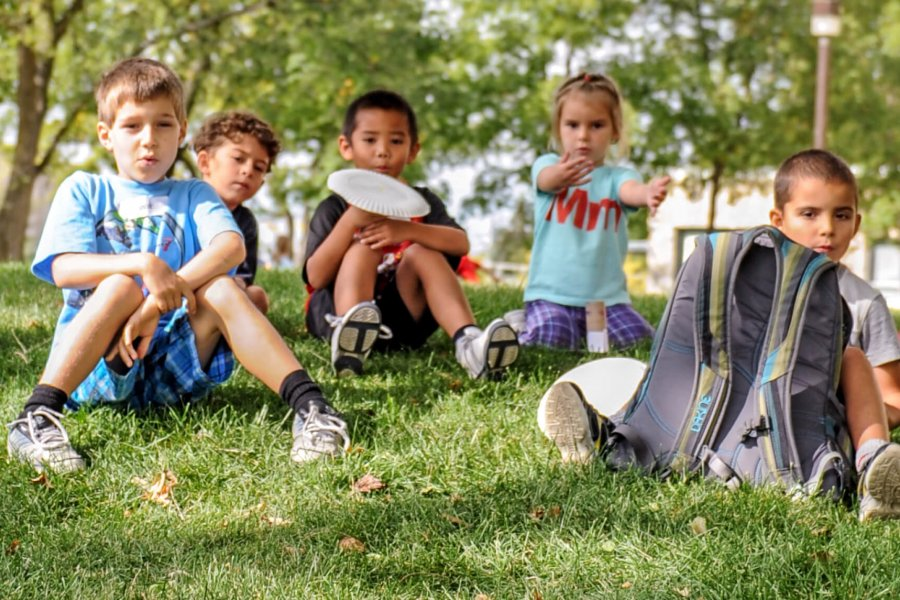 A group of children sitting outside in the grass together.