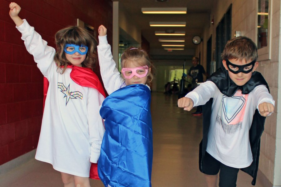 Three Mini U kids dressed as superheroes with masks and capes.