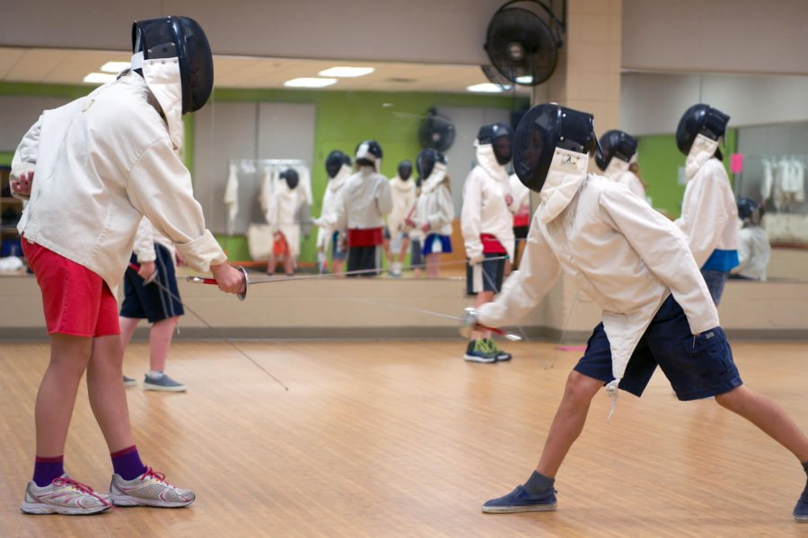 Kids practice their fencing techniques with each other.