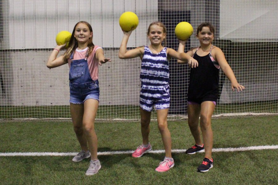 Three kids get ready to throw dodgeballs as the camera.