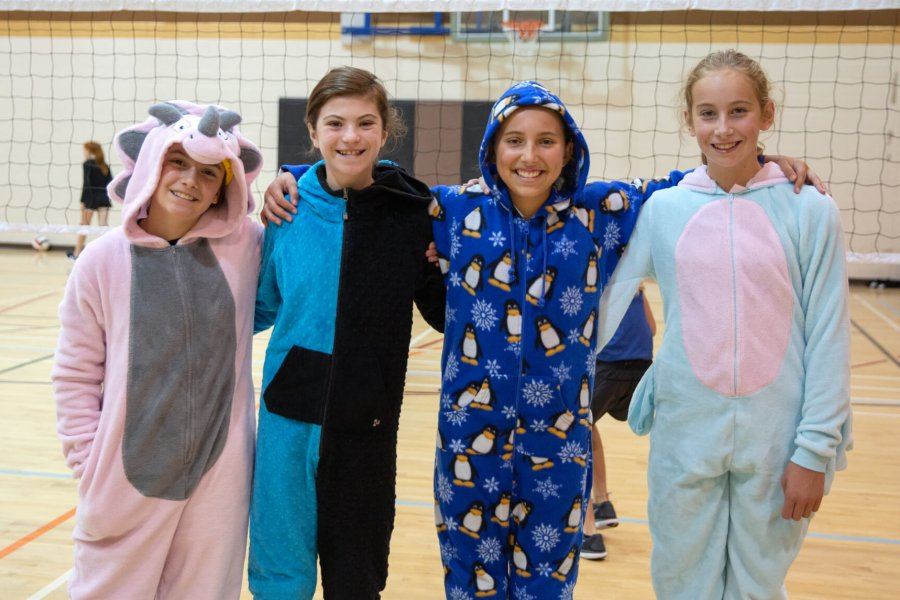 Four participants pose for a photograph wearing colourful, fun animal onesies.