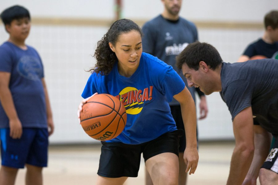 A junior program participant dribbles a basketball attempting to get past her opponent.