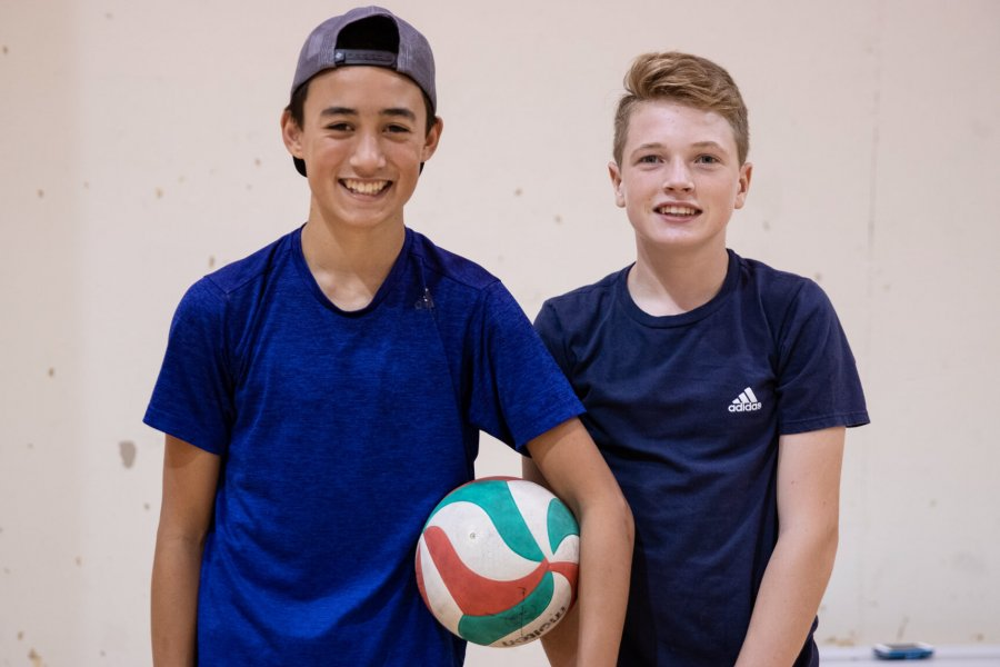 Two kids pose for a photo holding a volleyball.
