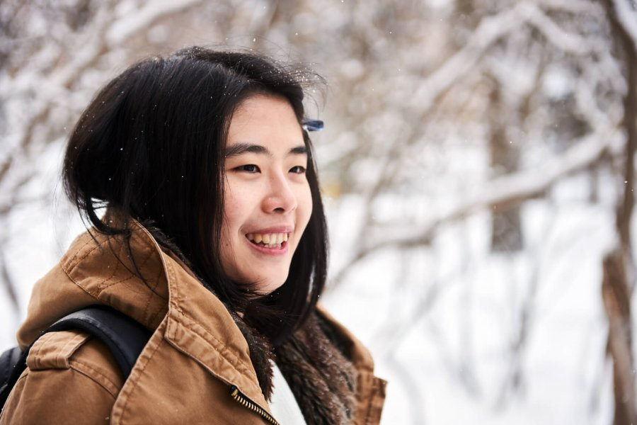 An international student stands smiling outdoors on a snowy winter day.