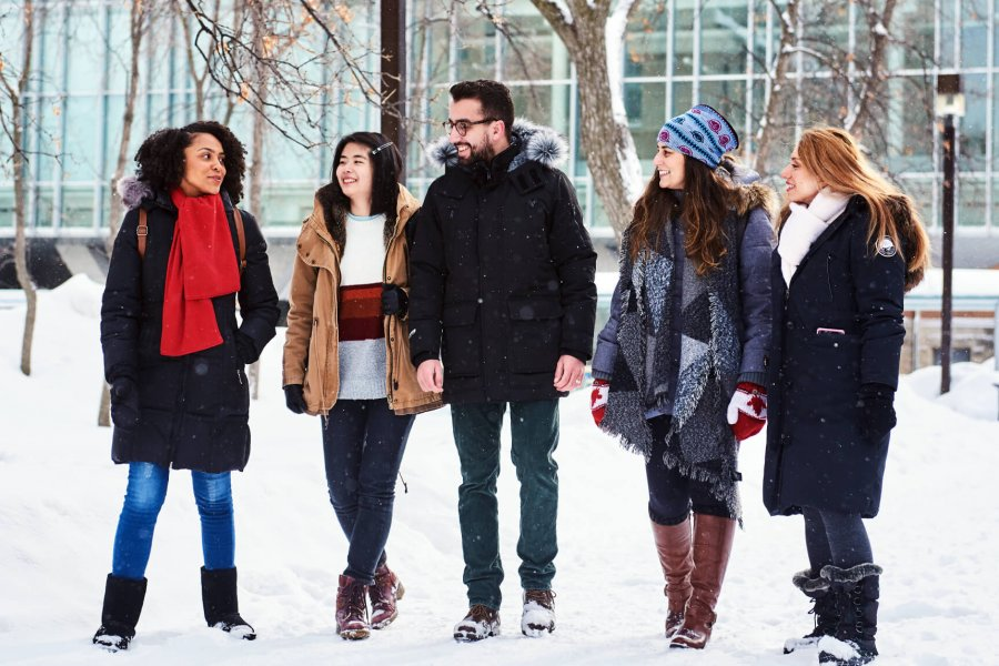 A group of 5 international students walk outdoors in the snow engaging in friendly conversation.