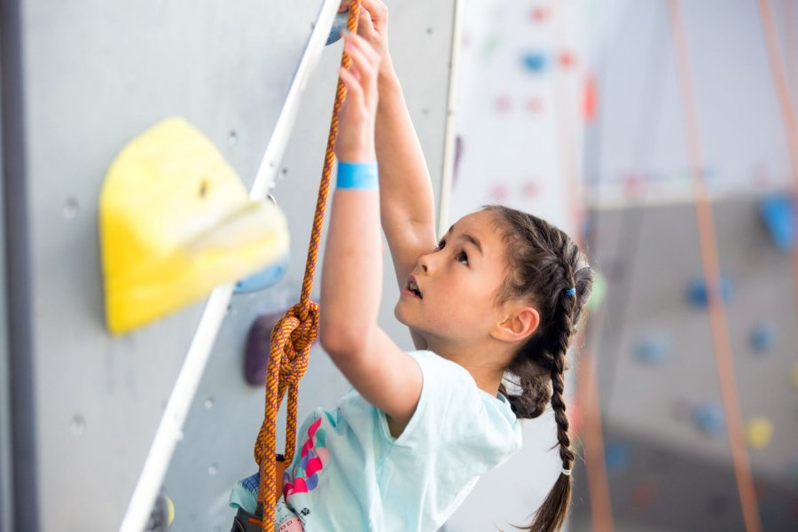 A young climber looks up to find a handhold while scaling a climbing wall.