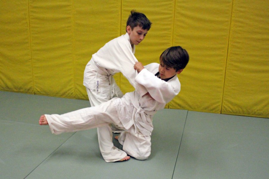 Two young judo participants engage in a match.