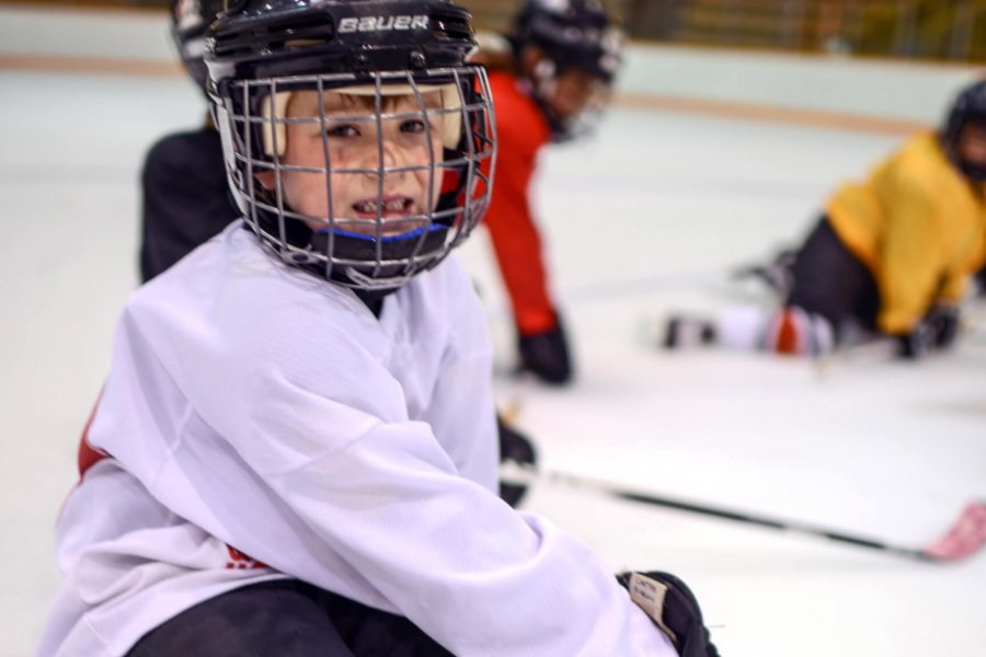 A beginner hockey player sits on the ice in full mask, hockey gloves, and jersey.