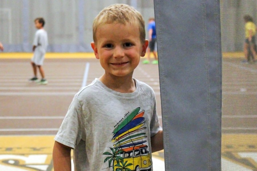 A smiling young soccer player stands on the sidelines of an indoor playing field.