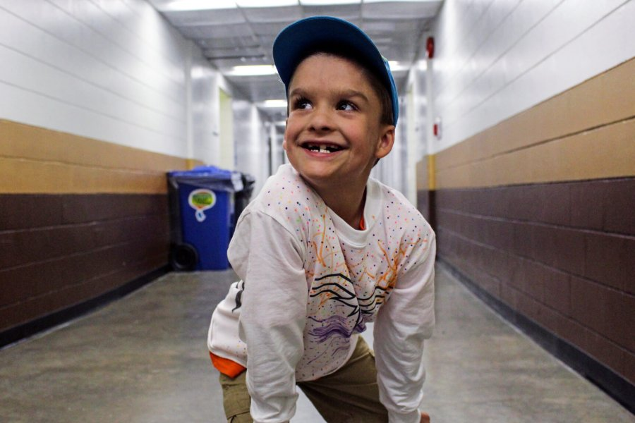 A smiling Mini U participant crouches in a hallway, eager to start.