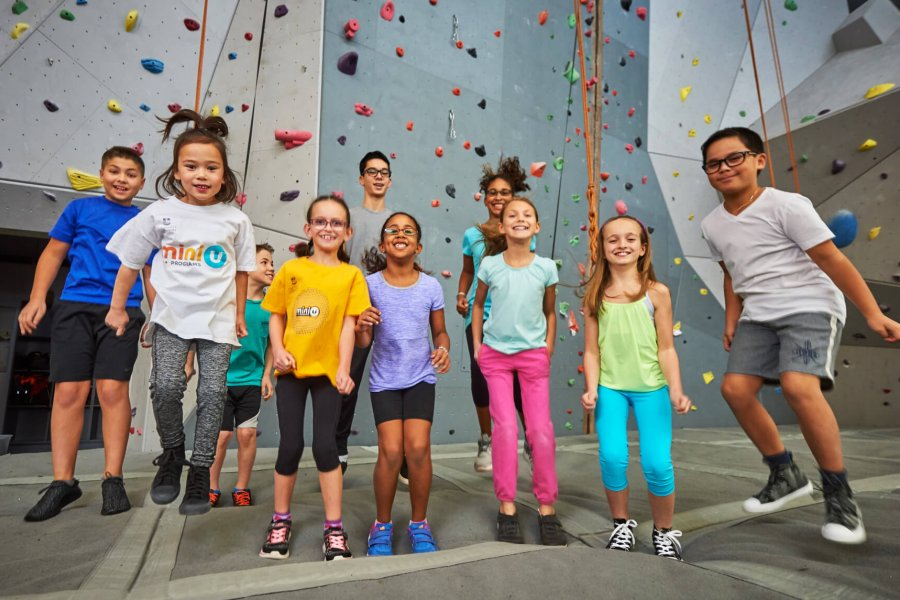A large group of children jump up and down with excitement in front of a climbing wall.