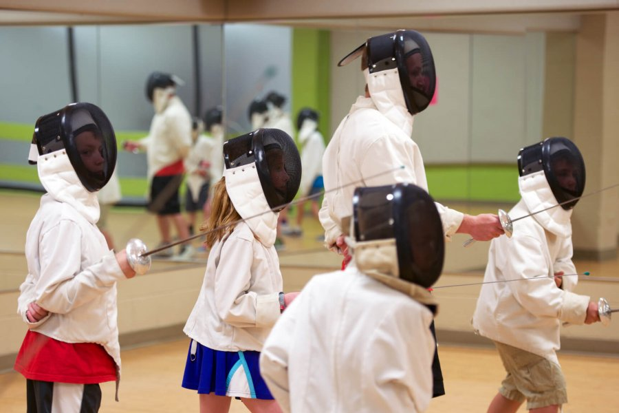 Four children wearing fencing masks and jackets practice their fencing skills guided by an instructor.