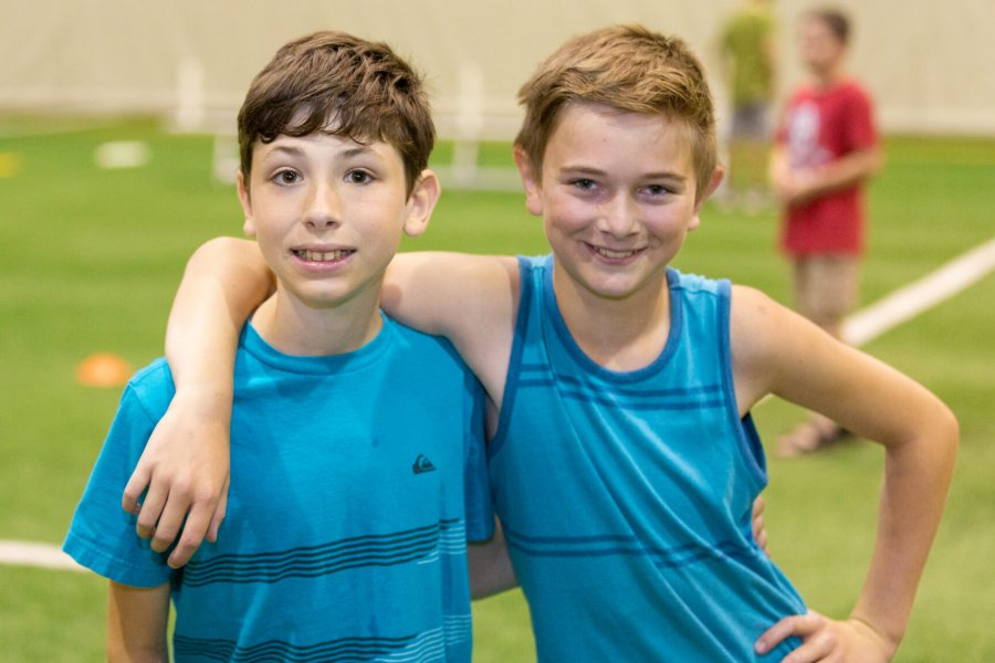 Two young athletes smile and pose arm in arm on an indoor field.