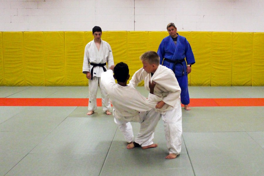 Two youths engage in a judo match as two instructors watch.