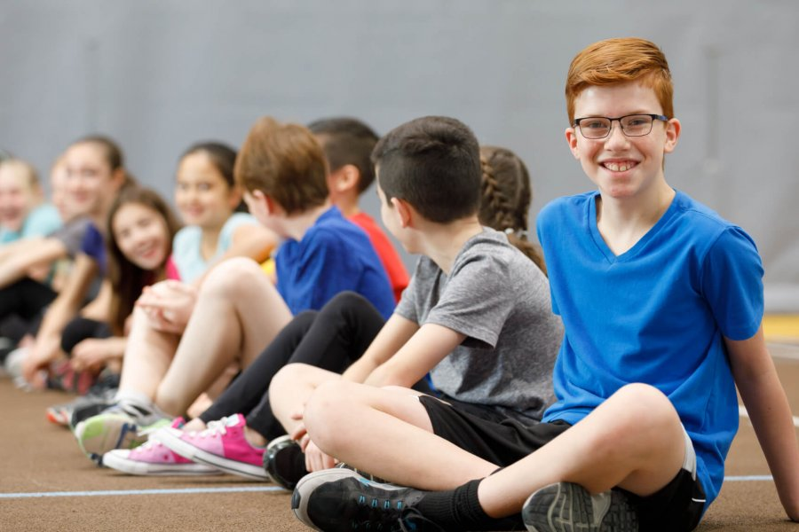 A group of Mini U participants sits on an indoor track. In the foreground, a smiling participant sits facing the camera.
