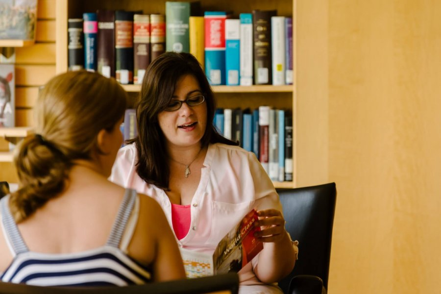A student consulting with an academic advisor in a library.