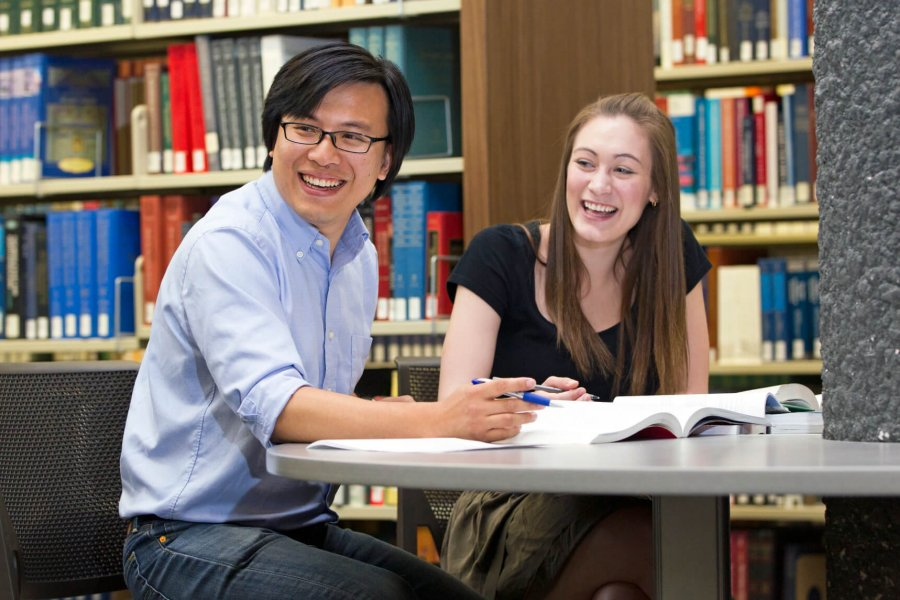 A student and tutor happily work together in a library.